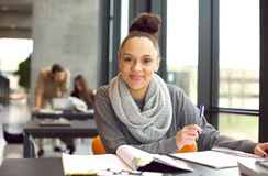 Confident female student studying in library. Confident young female student studying. Woman sitting at desk with books Stock Photography