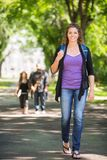 Confident Female Student Walking On Campus Road Stock Images