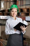 Confident Female Supervisor With Book At Warehouse Royalty Free Stock Photo