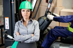 Confident Female Supervisor With Forklift Driver Royalty Free Stock Image