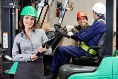 Confident Female Supervisor With Forklift Driver. Portrait of smiling female supervisor with foremen communicating at warehouse Royalty Free Stock Image