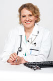 Confident female surgeon sitting idle, holding pen Royalty Free Stock Photography
