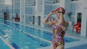 Confident female swimmer coming in swimming pool putting on her goggles for underwater floating, She wear swimsuit and. Confident female swimmer coming in stock video