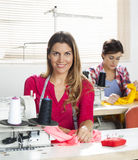 Confident Female Tailor Sitting At Workbench. Portrait of confident female tailor sitting at workbench in sewing factory with colleague in background Royalty Free Stock Photography