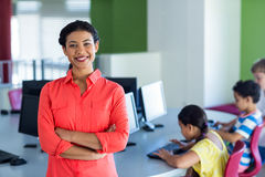 Confident female teacher with arms crossed standing in computer room Stock Images