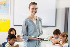 Confident female teacher with students. Portrait of confident female teacher with students writing in classroom royalty free stock photo
