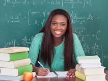 Confident female teacher writing in book at classroom desk. Portrait of confident female teacher writing in book at classroom desk royalty free stock photo