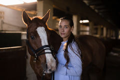 Confident female vet standing by horse in stable. Portrait of confident female vet standing by horse in stable Royalty Free Stock Images
