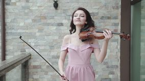 Confident female violinist walks in blowing, evening dress and plays on violin stock video