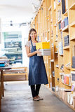 Confident Female Worker Carrying Boxes In Store Stock Photos
