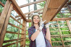 Confident Female Worker Carrying Wooden Planks Stock Photography