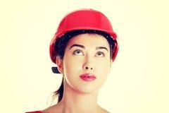 Confident female worker in helmet looking up. Stock Image