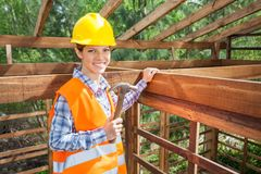 Confident Female Worker Holding Hammer In Timber Stock Photos