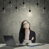 Confident female worker under light bulbs stock image