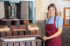Confident Female Worker Using Paper Press Machine Royalty Free Stock Photos