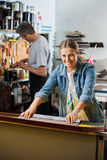 Confident Female Worker Using Squeegee In Factory Stock Photo