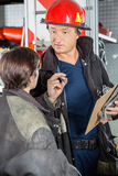 Confident Firefighter Discussing With Colleague Stock Photo