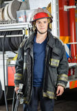Confident Firefighter Holding Hose At Fire Station Stock Photos