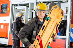 Confident Firefighter Holding Wooden Stretcher Royalty Free Stock Images
