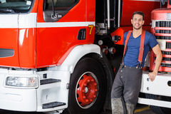 Confident Firefighter Leaning On Truck. Portrait of confident firefighter leaning on truck at fire station Royalty Free Stock Photos