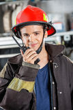 Confident Firefighter Using Walkie Talkie At Station Stock Photography