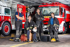 Confident Firefighters With Equipment At Fire. Portrait of confident firefighters with equipment against trucks at fire station Royalty Free Stock Photography