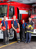Confident Firefighters Leaning On Trucks Stock Photo