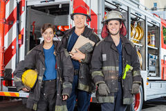 Confident Firefighters Standing Against Truck. Portrait of confident firefighters standing against truck at fire station Royalty Free Stock Photos