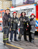 Confident Firefighters Standing Arms Crossed. Full length portrait of confident firefighters standing arms crossed at fire station Stock Image