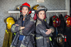 Confident Firefighters Standing Arms Crossed. Portrait of confident firefighters standing arms crossed at fire station Royalty Free Stock Photo