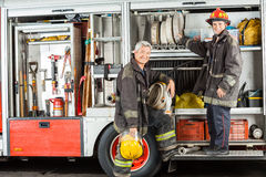 Confident Firefighters Standing On Truck At Fire. Portrait of confident male firefighters standing on truck at fire station Royalty Free Stock Photos
