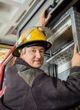 Confident Fireman Climbing Truck Stock Images