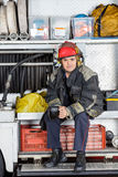 Confident Fireman Holding Coffee Mug In Truck Royalty Free Stock Image