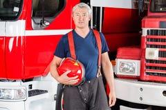 Confident Fireman Holding Red Helmet Stock Photo