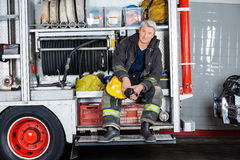 Confident Fireman Sitting In Truck At Fire Station Royalty Free Stock Photo