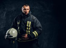 Confident fireman in uniform holding a helmet and looks into the camera royalty free stock photos