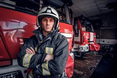 A confident fireman wearing protective uniform standing next to a fire engine in a garage of a fire department, crossed. Confident fireman wearing protective royalty free stock image