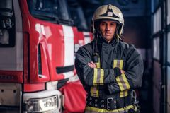 A confident fireman wearing protective uniform standing next to a fire engine in a garage of a fire department, crossed. Confident fireman wearing protective stock photo