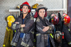 Confident Firemen Standing Arms Crossed. Portrait of confident young firemen standing arms crossed at fire station Royalty Free Stock Image