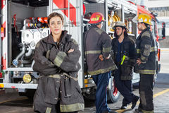 Confident Firewoman With Colleagues Standing By Stock Photography