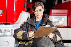 Confident Firewoman Holding Clipboard While Stock Photo