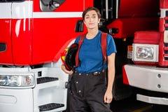 Confident Firewoman Holding Helmet Against Stock Image