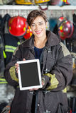 Confident Firewoman Showing Digital Tablet At Fire Station Royalty Free Stock Photography
