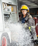 Confident Firewoman Spraying Water At Fire Station. Confident firewoman looking away while spraying water during training at fire station Royalty Free Stock Photography