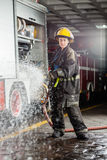 Confident Firewoman Spraying Water During Practice Royalty Free Stock Images