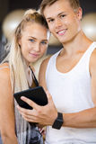 Confident Fit Couple With Digital Tablet Standing In Gym Royalty Free Stock Photo