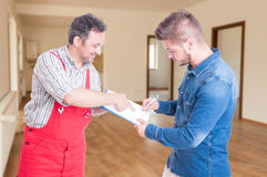 Confident fitter giving clipboard with contract to client Stock Photo