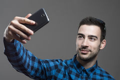 Confident flirty young man taking high angle selfie portrait Stock Image