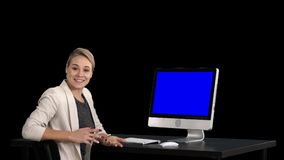 Confident focused businesswoman talking to camera and looking to monitor near her, Alpha Channel. Blue Screen Mock-up. On Alpha Matte. View to the screen of stock video footage