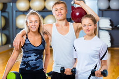 Confident Friends Lifting Weights In Gym Stock Photos